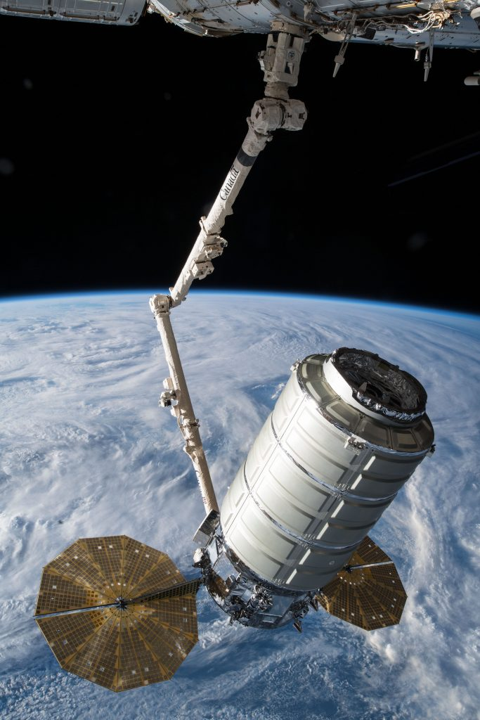 The Orbital ATK space freighter is slowly maneuvered by the Canadarm2 robotic arm